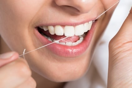 Closeup of young woman flossing teeth at home